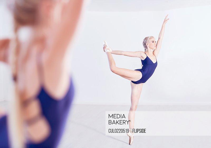 Mirror image of young female ballet dancer en pointe in dance studio