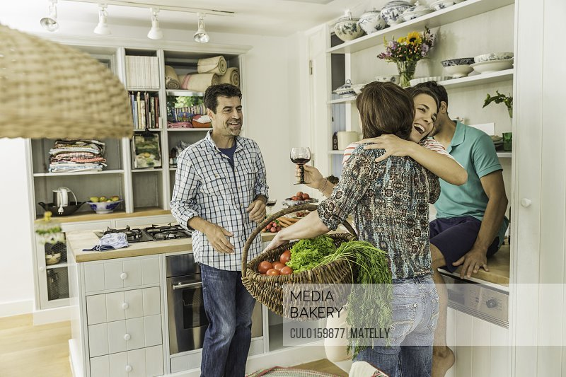 Four adult friends greeting in kitchen