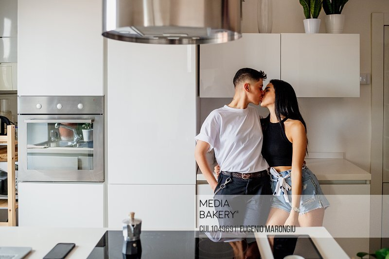 Young lesbian couple standing in kitchen, kissing.