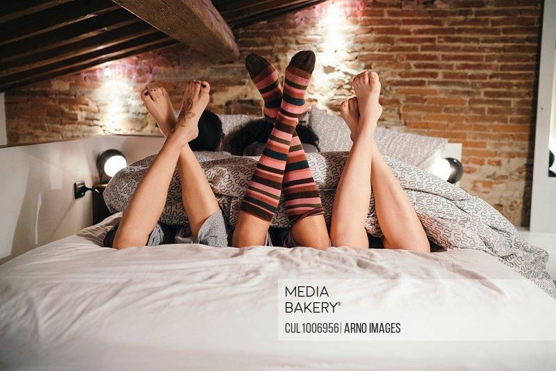 Crossed legs of friends lying side by side on bed