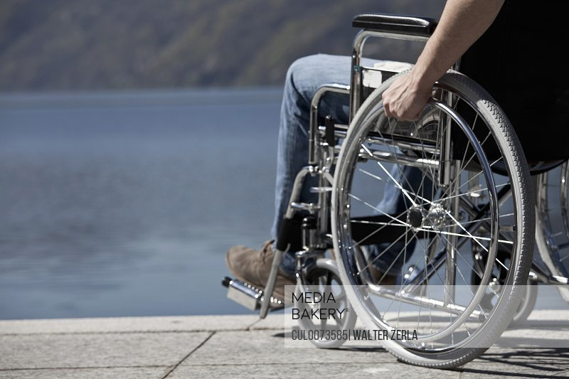 Man in wheelchair sitting by water
