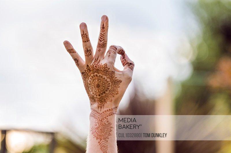 Hand with henna tattoo making gesture