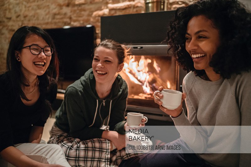 Friends in front of fire drinking coffee smiling
