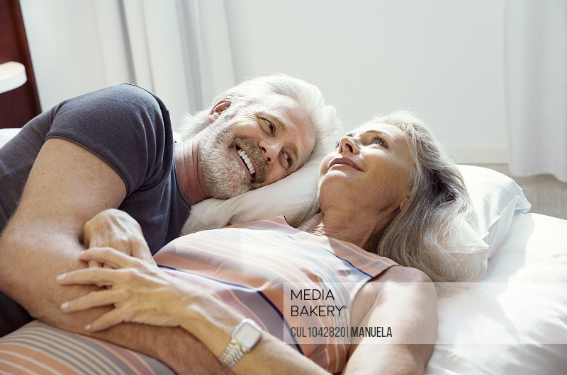 A couple lying on a bed together and smiling.