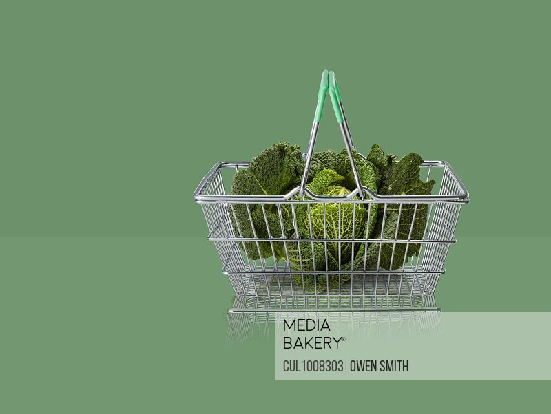 Green cabbage in miniature shopping basket on green background