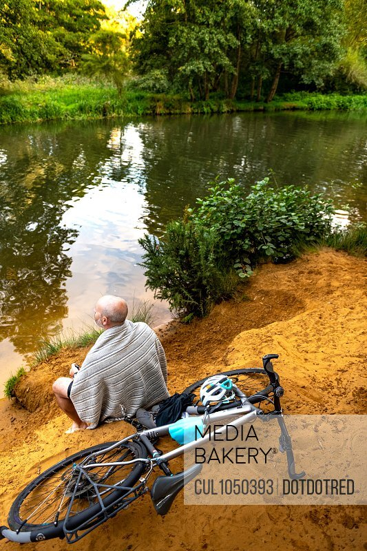 Swimmer sitting beside river with bicycle