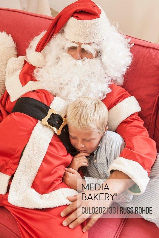 Man sitting on sofa dressed as santa hugging boy