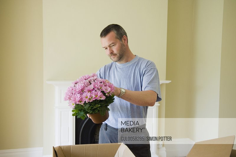 Man unpacking flowers in new home
