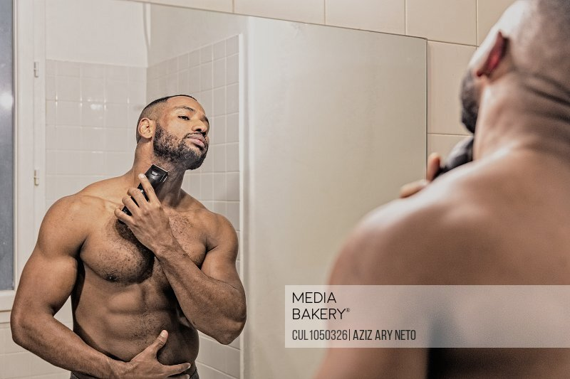 Man shaving with electric razor, looking in mirror