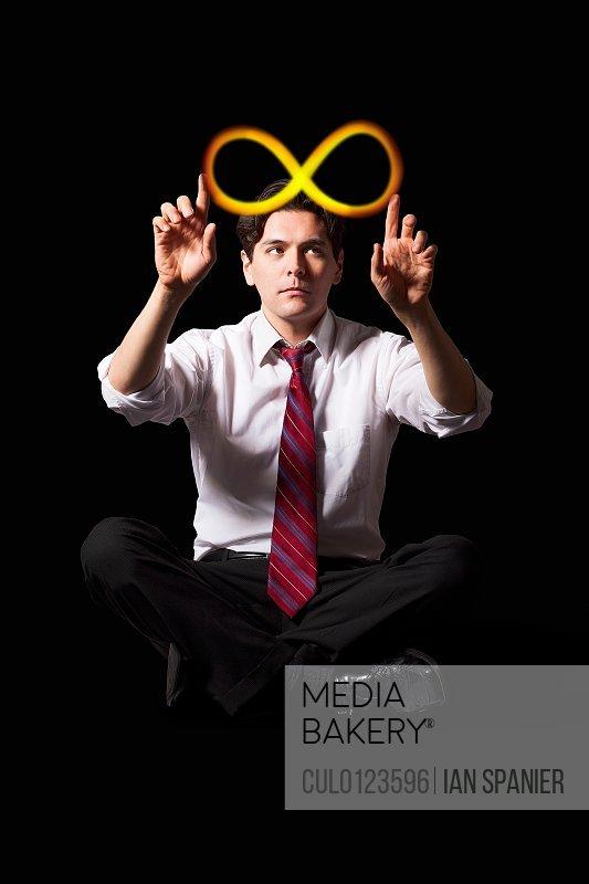 Businessman touching illuminated infinity symbol/n