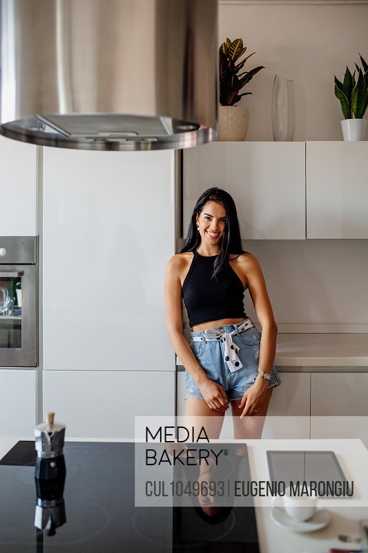 Portrait of young woman with long brown hair, wearing hot pants, standing in kitchen.