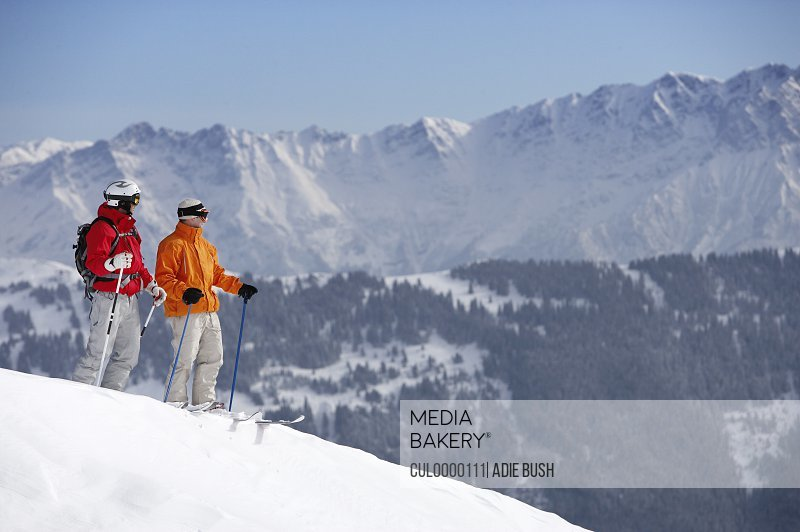 two male skiers on slope looking towards mountains