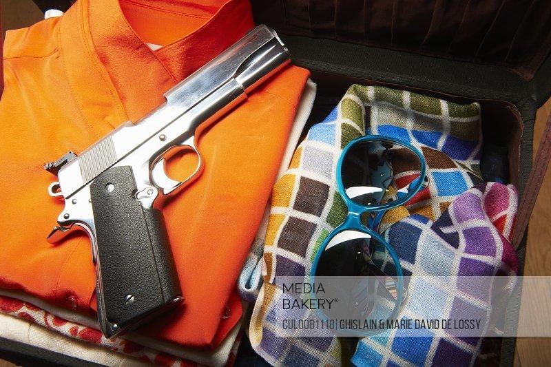 Gun and sunglasses in suitcase