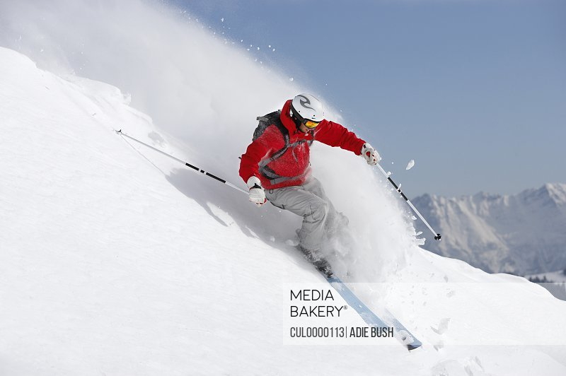 male skier turning in snow on slope