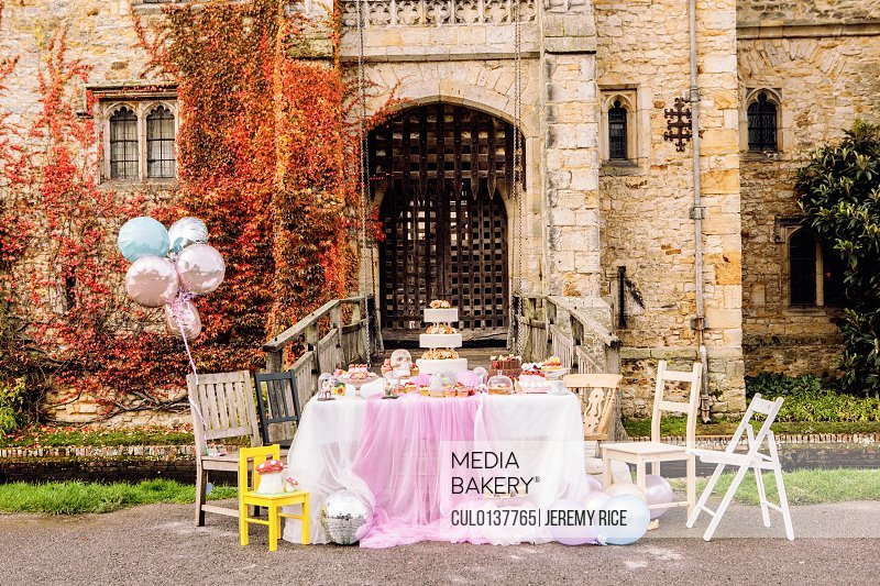 Table and balloons outside castle