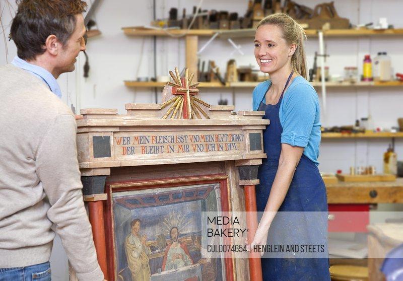 Carpenters carrying antique art piece