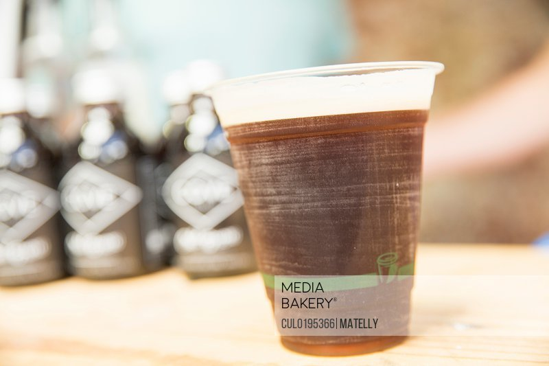 Cup and bottles of cold brew coffee on cooperative food market stall