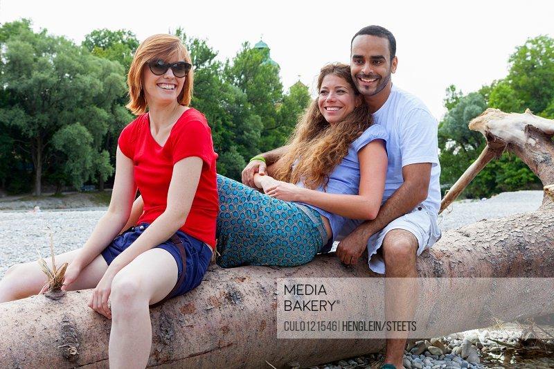 Three friends sitting on log/n