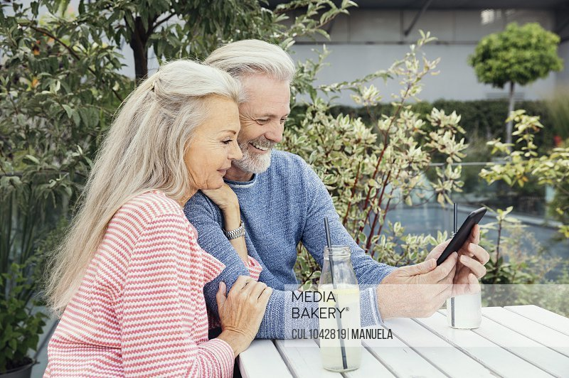 A couple sitting at a table in a garden with drinks in bottles, looking at a mobile phone together.
