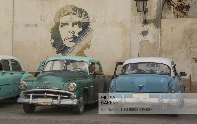 Vintage cars parked under portrait of Che Guevara, Havana, Cuba