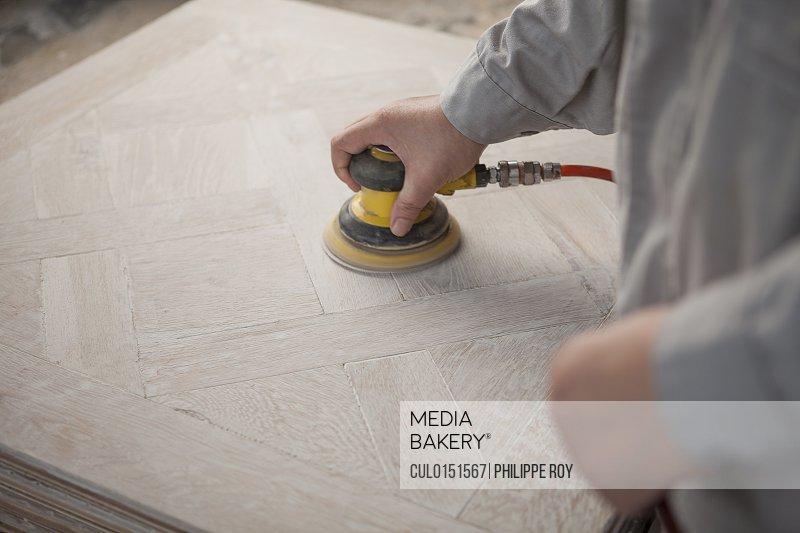 Carpenter smoothing surface of wood plank in factory Jiangsu China