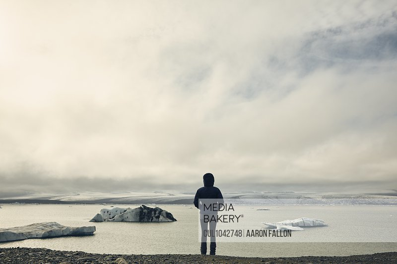 A woman on a stony beach looking out to sea and ice floes.