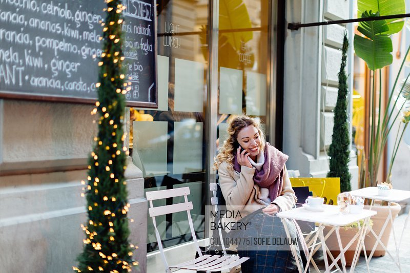 Woman using smartphone at cafe, Firenze, Toscana, Italy