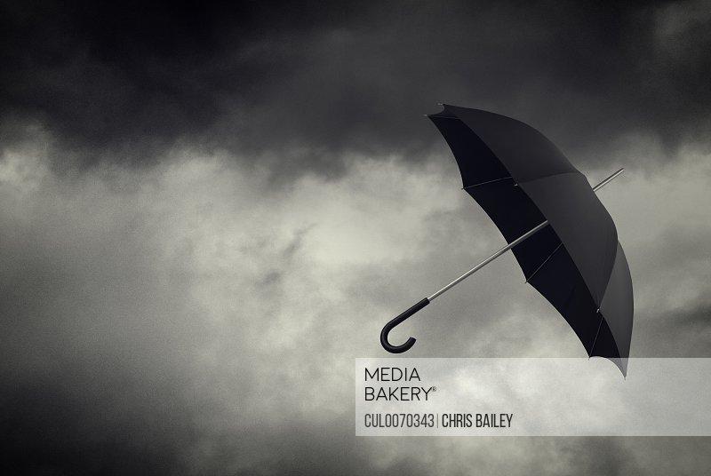 Umbrella floating in stormy sky