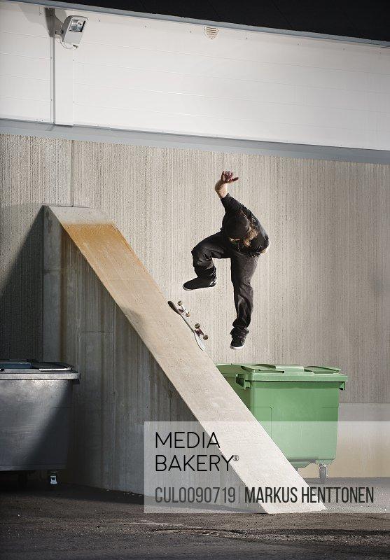 Man skating on urban ramp