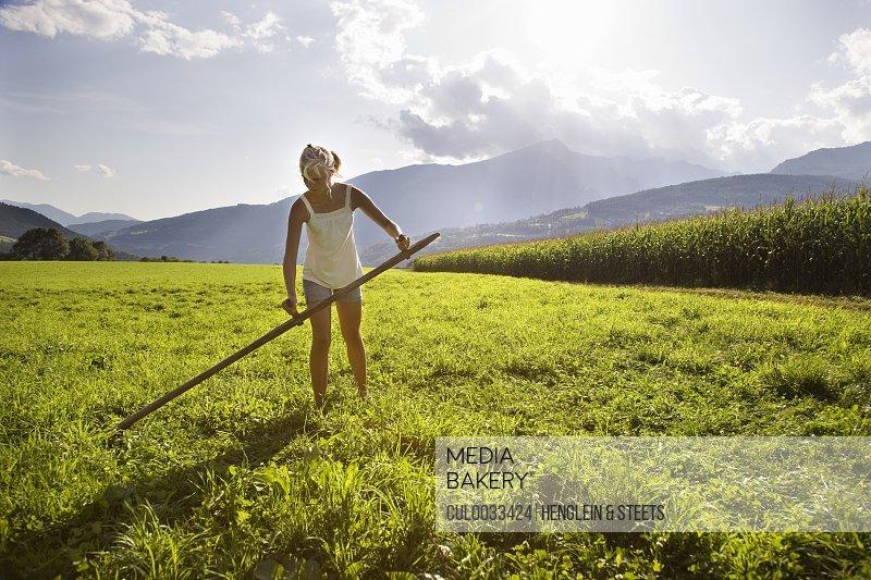 girl cutting grass with scythe