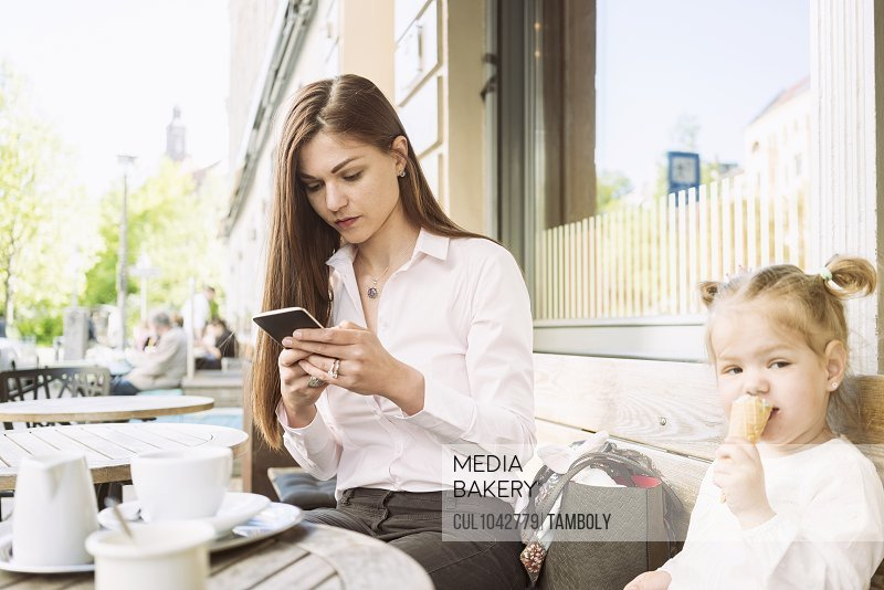 A mother and daughter sitting outside a cafe, mother on her mobile, daughter eating an ice cream.