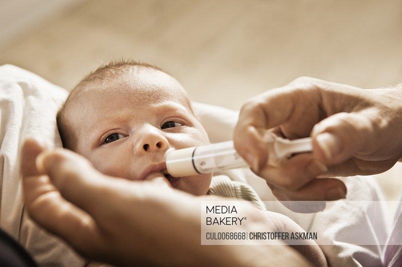 Parent feeding infant with syringe