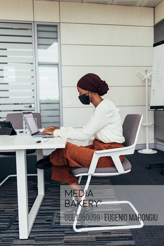 Businesswoman wearing face mask, working in office