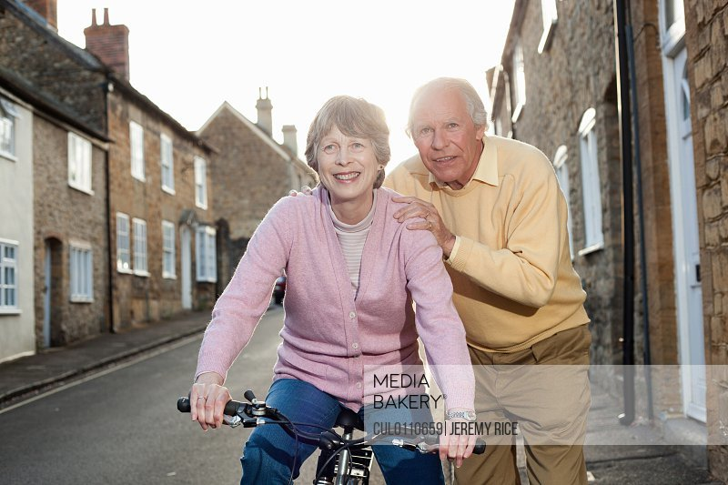 Husband supporting wife on bicycle