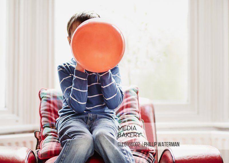 Young boy holding balloon in front of face