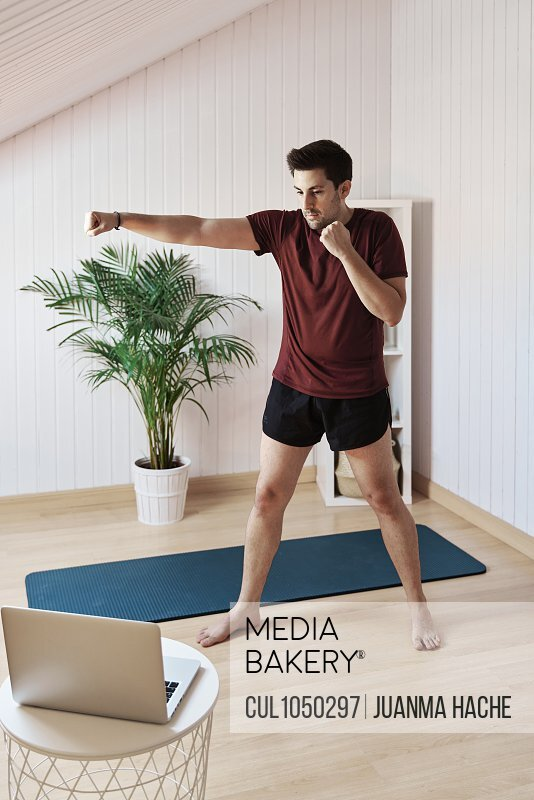 Man following online exercise class, punching movement