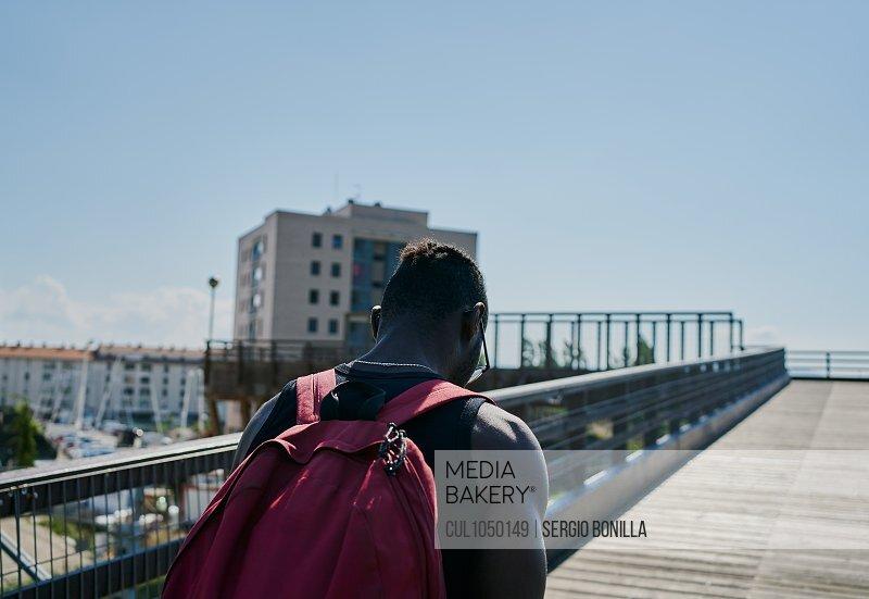 Young man walking across bridge
