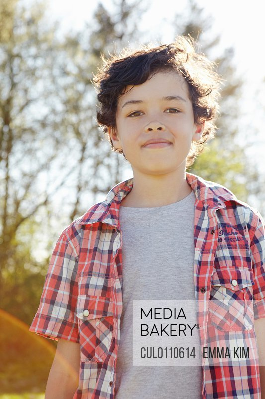 Boy wearing checked shirt in park