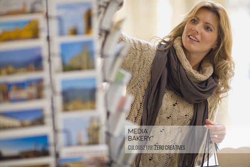 Woman viewing postcard holder