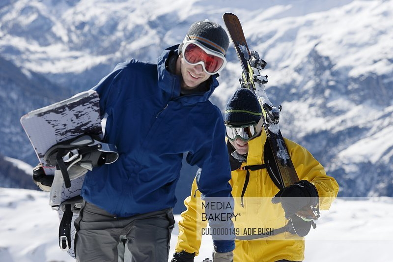 Male skier and male snowboarder walking up mountain ridge carrying skis