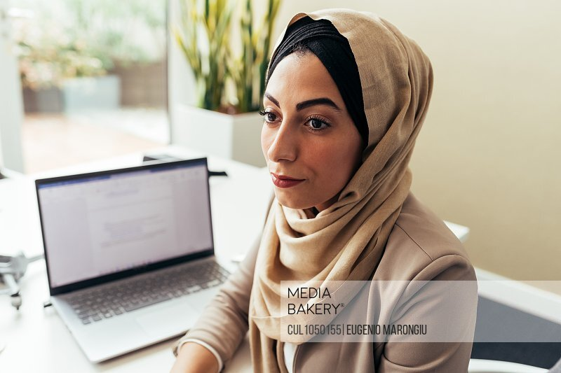 Businesswoman in office with laptop