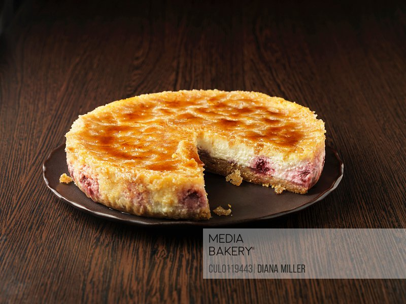 Lemon and raspberry brulee cheesecake on dark brown plate and surface/n