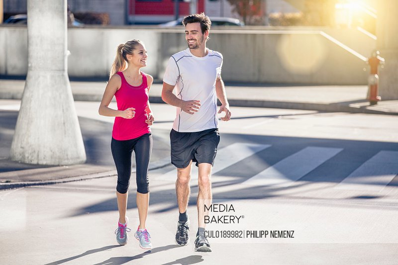 Couple wearing sports clothing jogging in urban area smiling