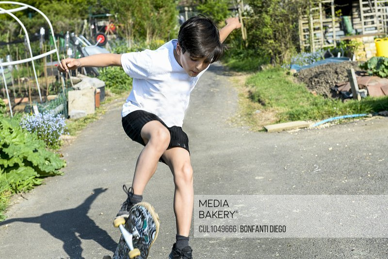 Boy with brown hair wearing t[shirt and shorts performing skateboard trick.