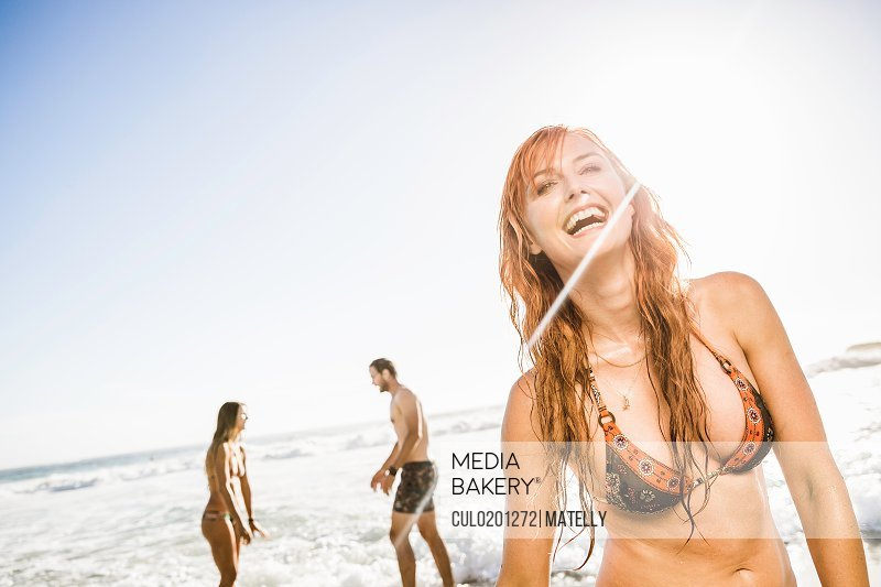 Mid adult woman wearing bikini top laughing on beach Cape Town South Africa