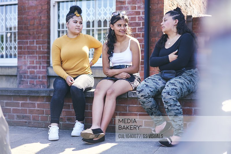 Young woman and her teenage sisters sitting on wall talking