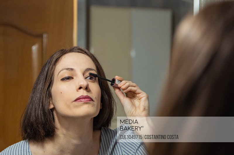 Woman standing in front of mirror, applying makeup