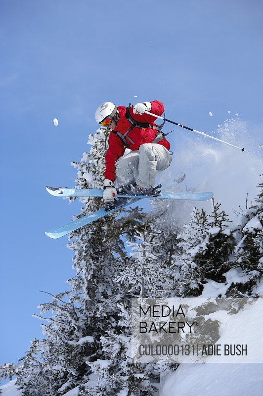 male skier jumping through trees with skis crossed
