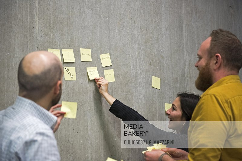 Students using sticky notes on wall to brainstorm ideas