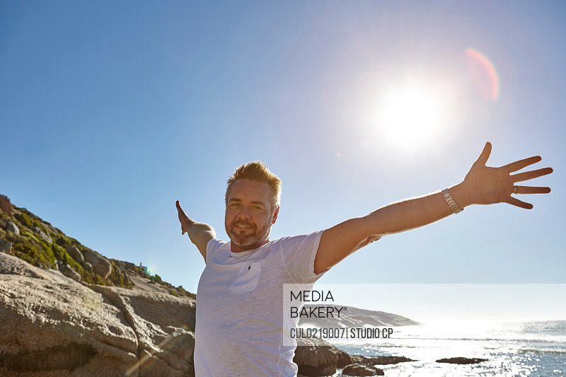 Portrait of mature man on beach arms outstretched Cape Town South Africa